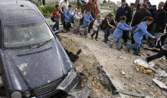 Schoolchildren passed a damaged car at the site of an explosion in Mieh Mieh refugee camp that killed Fatah's Kamal Madhat.