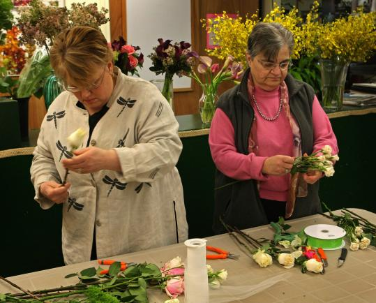 Leah Delinger (left) and Faith Cass teach brides-to-be to create their own bouquets.