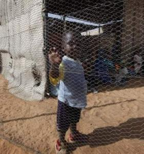 A displaced Sudanese child walked behind the fence of a clinic at Zamzam refugee camp on Monday.