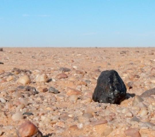 Students found this black rock chunk from an asteroid in a Sudan desert, and it is probably billions of years old.
