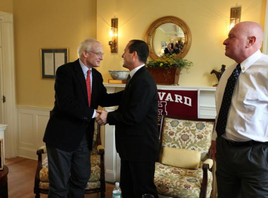 Harvard professor Michael Porter (left) greets Nir Barkat (center), mayor of Jerusalem. On the right, business strategist Yagil Weinberg.