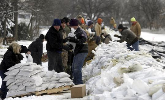 Allen Fredrickson/REUTERSVolunteers in Fargo, N.D., worked in temperatures barely in the double digits yesterday to place sandbags in an effort to heighten an earthen dike near the Red River. The w