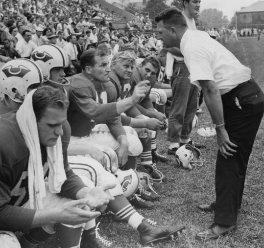 Lou Saban talked to Patriots quarterback Butch Songin (with hand up) during an exhibition game in 1960. The team, hampered by a late start in recruiting, went 5-9 in its first season.
