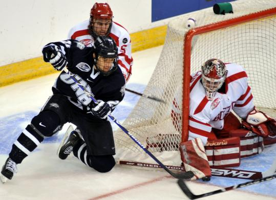 Boston University goalie Kieran Millan (27) saves was able to withstand this scoring bid by New Hampshire's James van Riemsdyk.