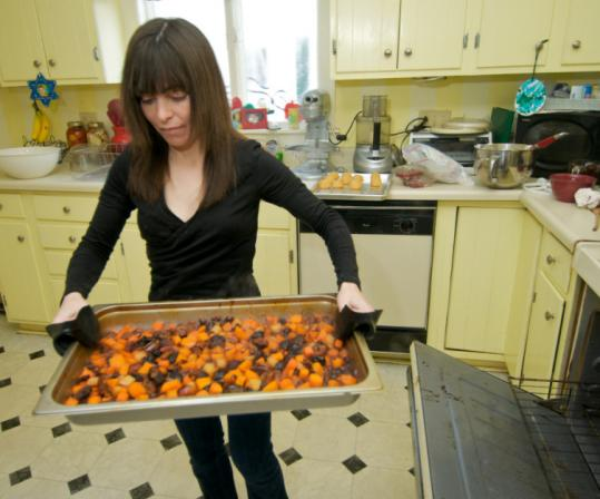 Caterer Dawn LaRochelle carries a tray of tsimmes.