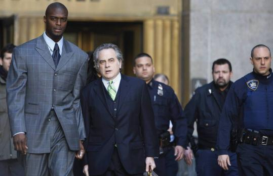 Plaxico Burress and lawyer Ben Brafman (center) leave a Manhattan court after his gun possession case was pushed back.