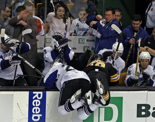 Tampa Bay's Matt Pettinger (left) and the Bruins' Matt Hunwick either are searching for a contact lens or they're about to land on the Lightning bench.