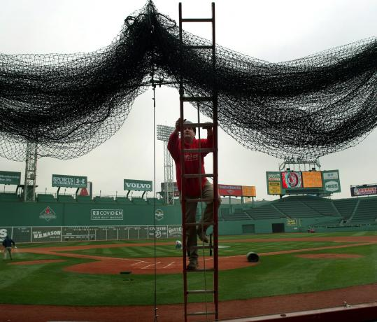 HANGING IN THERE - Getting Fenway Park's game face on, ironworker Kevin Mcconologue stands astride a ladder as he hangs the netting behind home plate in preparation for the Red Sox' opener against the Tampa Bay Rays Monday.