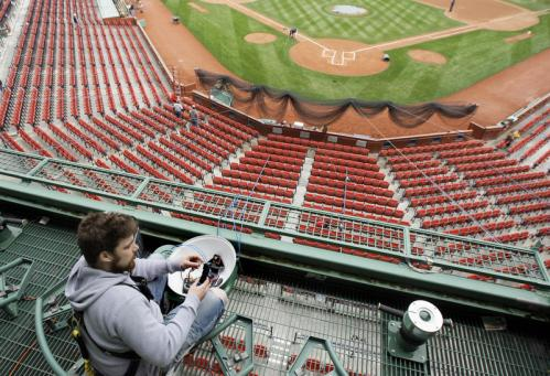 Eric Sigman, of Custom Cable Co., hooked up a video camera for the Red Sox hitting coaches high up behind home plate at Fenway Park on Thursday.