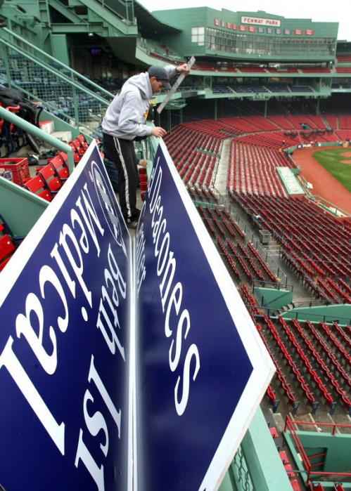 A worker prepares to hang an advertising sign for Beth Israel Deaconess Medical Center at the right field roof box seats.