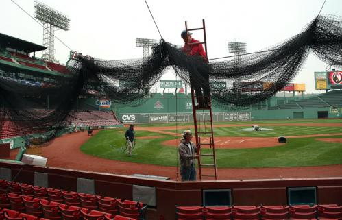 Iron worker Kevin McDonologue, from Somerville, stood on a ladder as he hung a foul ball net behind home plate. Scott White from Kingston held the ladder.