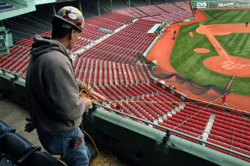 In preparation for Monday's Opening Day at Fenway Park, iron worker Scott White, from Kingston, pulled a rope attached to the backstop netting that was being installed behind home plate.