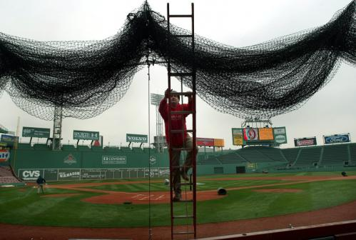 Iron worker Kevin McConologue, from Somerville, stood on a ladder as he hung the backstop foul ball net.