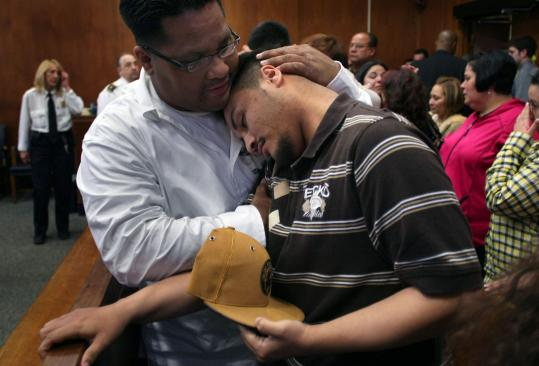 JOHN TLUMACKI/GLOBE STAFFSergio Roman wept as he was hugged by his uncle, Isaias Roman, after a man was convicted of killing Sergio's mother, Noemi.