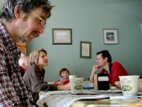 Francis Doiron read the Globe at Breads 'n Bits of Ireland in Melrose yesterday while the Locke family ate in the background. Steven Locke said ''it'd be a tragedy if the Globe were to close,'' while his wife, Suzanne, thought about a world in which her children didn't know newspapers.