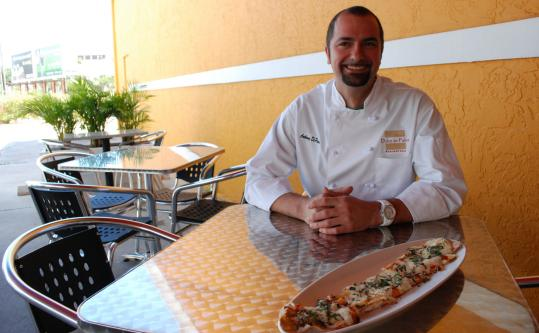 Medfield native Anthony de Palma with margherita flatbread at his restaurant, Dolce de Palma, in West Palm Beach, Fla.
