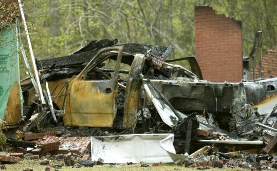 The remains of Kevin and Tammy Garner's home and a burnt vehicle yesterday in Priceville, Ala.