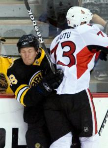 Matt Hunwick has a glassy look as he gets hammered into the boards by the Senators' Jarkko Ruutu.