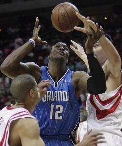Dwight Howard coughs up the ball as Houston's Yao Ming (right) and Shane Battier (left) apply the pressure.