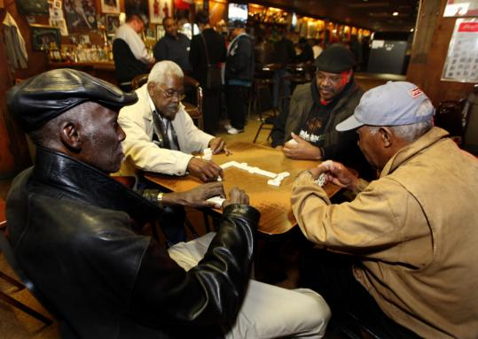 From left, Booker T Hunt, Brad Jones, Nick Simpson, and an unidentified man played dominoes Monday at Packy Connors in Roxbury.