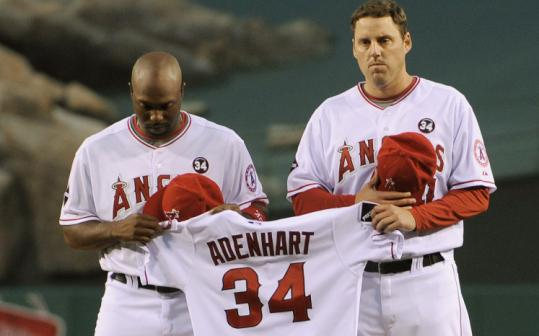 Torii Hunter (left) and John Lackey hold Nick Adenhart's jersey during pregame ceremonies last night.