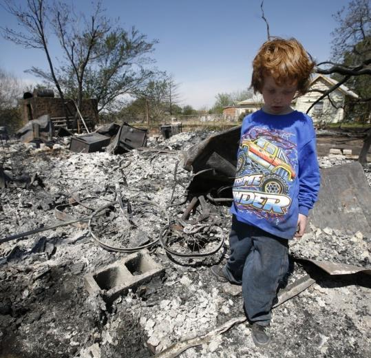 Reuven Raper-Ostrow, 7, walked through the rubble of his burned out home after he and his family returned to the area Friday i