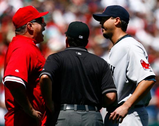 With umpire Ed Rapuano playing peacemaker, Angels manager Mike Scioscia expresses his displeasure to Josh Beckett.