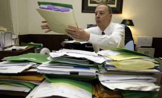 Attorney Bryan Elliott looks over bankruptcy files at his office in Hickory, N.C. ''There's no end in sight,'' he says.