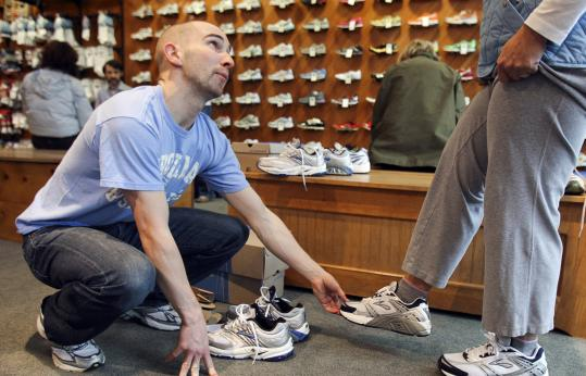 Sales associate Rob Dalton helps customer Andrea Griffin try on running shoes at Marathon Sports in Wellesley.