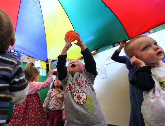 Toddlers play under a parachute yesterday at the Allston-Brighton Family Network, a playgroup coordinated by Family Nurturing Center.