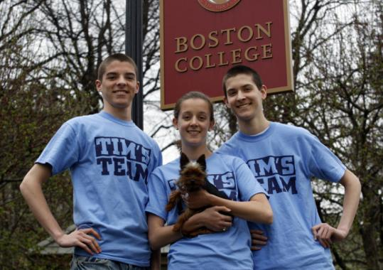 Stephen, Kristen, and Michael Padulsky with their Yorkshire terrier in front of Boston College on Saturday. Stephen and Kristen are running the Boston Marathon today for their late brother Tim.