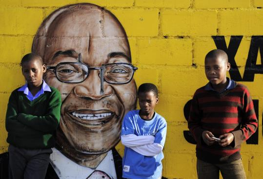 South African boys in front of wall portraying ANC leader Jacob Zuma, the favorite to win today's presidential election.