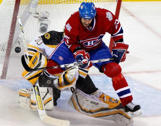 Mathieu Dandenault tries to screen Tim Thomas during the first period, but the Bruins goalie is having none of it.
