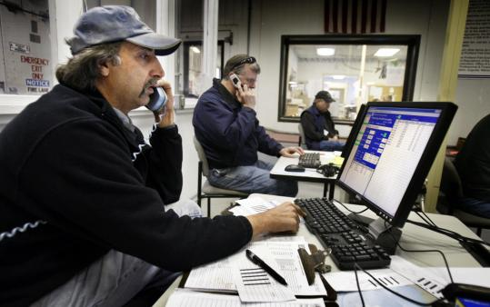 Nick Avelis (left), a fish buyer for Cape Ann and Smitty's Seafood, made a bit by computer at the auction at the Portland Fish Exchange in Portland, Maine, earlier this month.