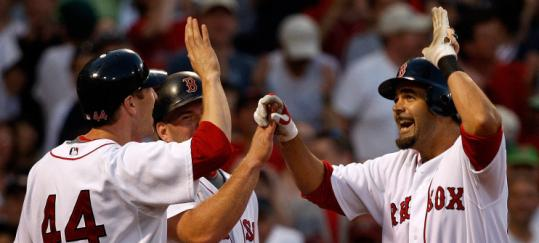 Mike Lowell (right) offers high-fives all around following his game-changing three-run homer in the seventh inning.