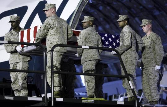 A Marine Corps team carried the case containing the remains of Marine Corporal William C. Comstock at Dover Air Force Base.