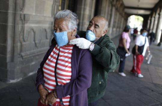 A man helped a woman put on her mask yesterday in Mexico City, where schools and movie theaters are closed.