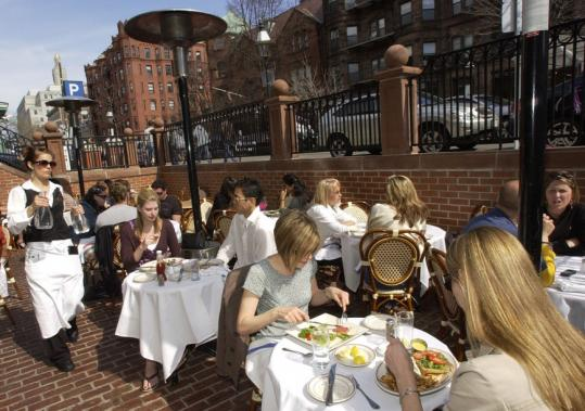 A crowd enjoyed outdoor dining on an April day on Newbury Street in this file photo. Current law limits outdoor tables to May to October.
