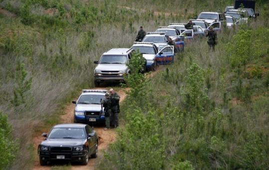 Law enforcement agents worked near a wooded area where the Jeep belonging to murder suspect George Zinkhan was found.