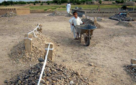 An Afghan boy pushed a handcart among new graves of people killed after air strikes in Ganj Abad of Bala Buluk district in Farah Province on Monday. The United States is investigating the deaths and Pakistan is targeting a valley held by militants. A8