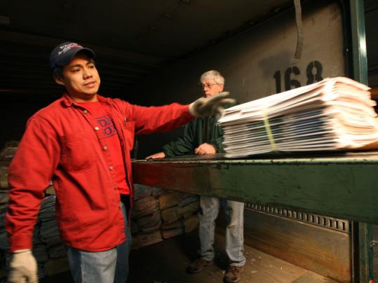 Esteban Jaimes (left) and Edward Parrish, members of the Teamsters union, loaded papers yesterday.