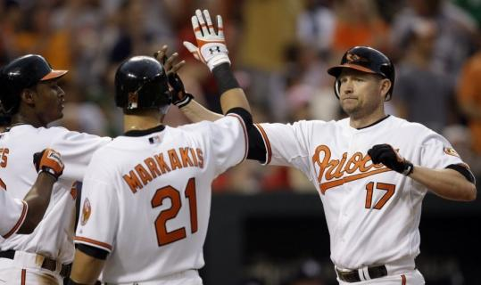 Adam Jones (left) and Nick Markakis are glad to see Aubrey Huff, who brought them home with a three-run homer in Baltimore's big second inning.