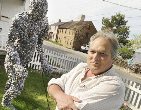 Michael Updike poses with his sculpture made of mussel shells on the lawn outside his apartment in Newburyport.