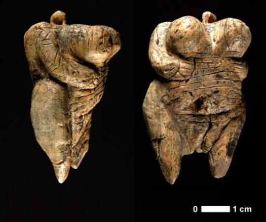 Side and front views of a sculpture of a woman found in the Hohle Fels cave in Germany.