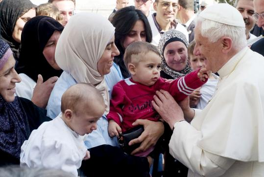 Pope Benedict XVI greeted Palestinians in the West Bank city of Bethlehem yesterday. The pope lamented the ''tragic'' building of walls as he stood in the shadow of Israel's steel and concrete separation barrier in a Bethlehem refugee camp