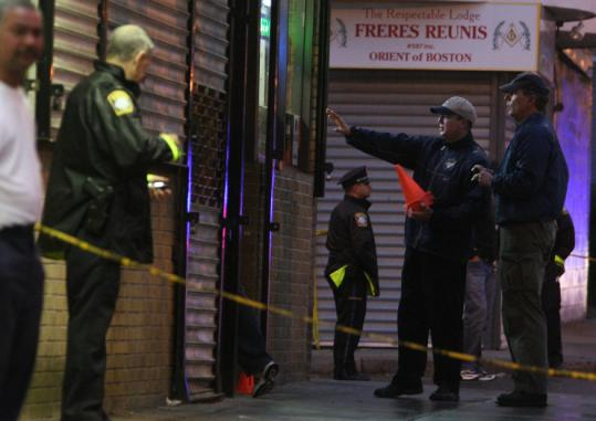 Essdras M Suarez/ Globe StaffBoston police outside O.M. May Liquors, where a woman and a child were injured by shots fired through the shop window.