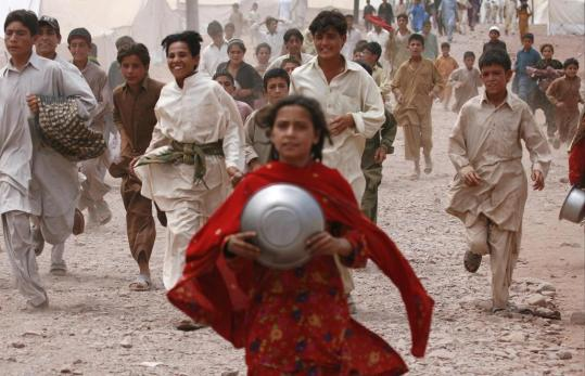 Refugee children chased after food donations at a United Nations camp on the outskirts of Peshawar yesterday.