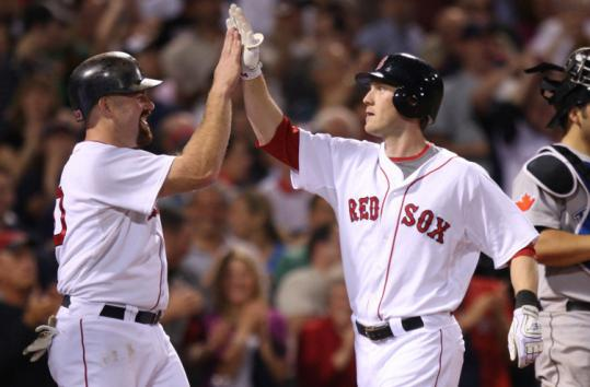 Kevin Youkilis, who went 3 for 5, salutes Jason Bay after his two-run homer in the Red Sox' sixth-run fifth inning.