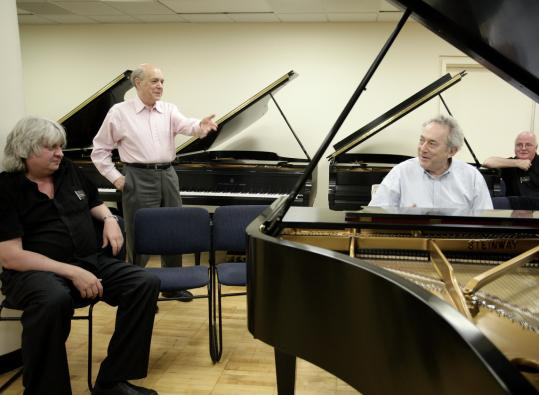 Victor Rosenbaum (second from left) and Gabriel Chodos (at piano), members of the piano faculty at the New England Conservatory, tried out instruments in Long Island City, N.Y.