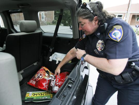 Detective Meredith Lobur loads her car for deliveries from the pet food pantry at the Southborough Police Department. She got the idea while working for the MSPCA.